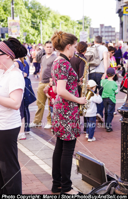 Stock photo - A young woman play saxophone in a central street of Dublin