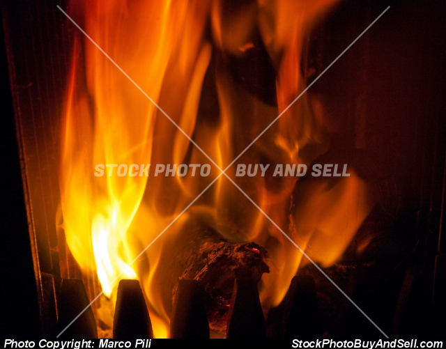 Stock photo - Fire burns wood logs inside a stove