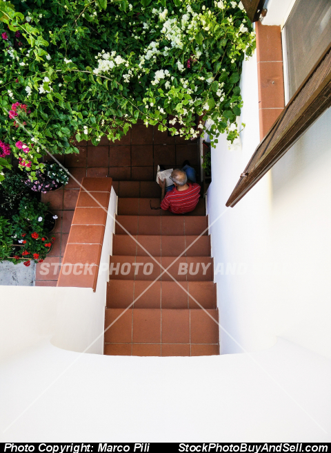 Stock photo - Senior man sitting on the stairs playing a sudoku scheme