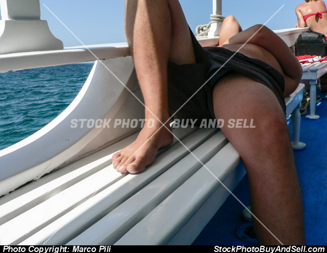 Stock photo - A half-naked sailor sleeps on the white bench of a fishing boat on a tourist trip