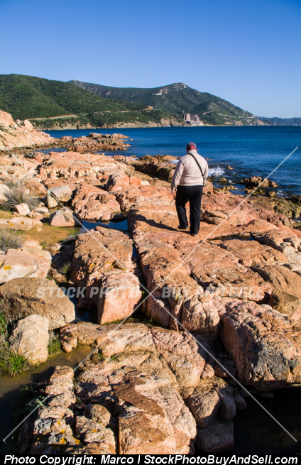 Stock photo - Man walking on the rocks in front of the Mediterranean Sea