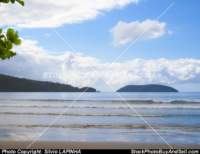 Ubatuba, Brazil. Beach and sea with waves, and island in the background.