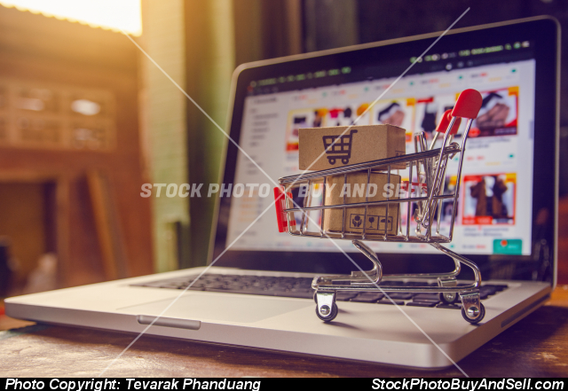 Stock photo - Shopping online concept - Parcel or Paper cartons with a shopping cart logo in a trolley on a laptop keyboard. Shopping service on The online web. offers home delivery.